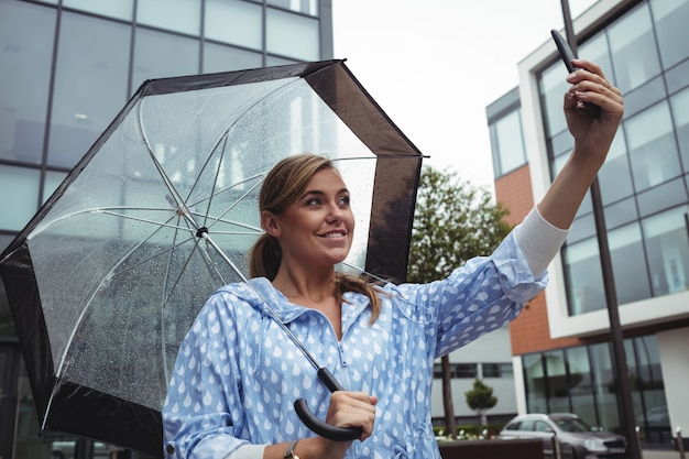 Mulher bonita que guarda o guarda-chuva ao tomar o selfie Foto gratuita