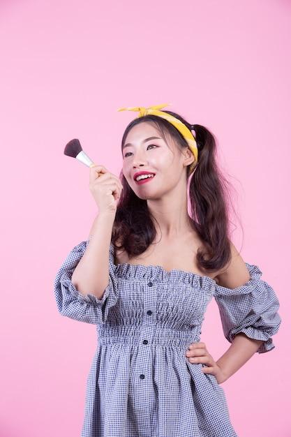 Mulher bonita que guarda uma escova, escovada em um fundo cor-de-rosa. Foto gratuita