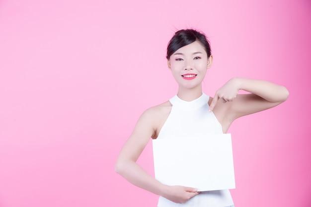 Mulher bonita que guarda uma folha da placa branca em um fundo cor-de-rosa. Foto gratuita