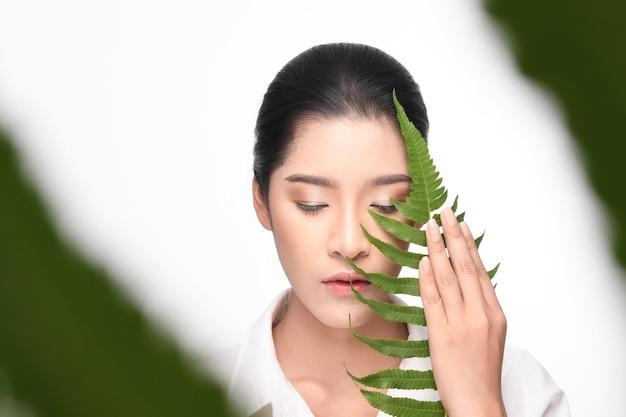 Mulher bonita que prende a planta verde. Foto Premium