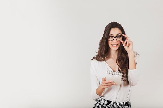 Mulher bonita que prende uma agenda e tocando seus óculos Foto gratuita