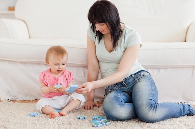 Mulher bonita que segura seu bebê em seus braços enquanto está sentada em um tapete Foto Premium