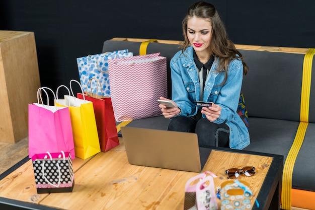Mulher bonita que senta-se em casa com dispositivos eletrónicos; sacos de compras e cartão de crédito na mão Foto gratuita