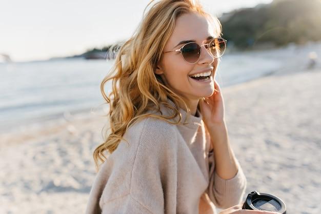 Mulher bonita realmente ri, relaxando na praia. mulher blinde de óculos e suéter segura uma xícara de café. Foto gratuita