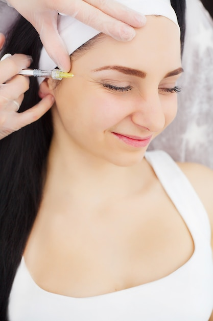 Mulher bonita recebe injeções, cosmetologia Foto Premium