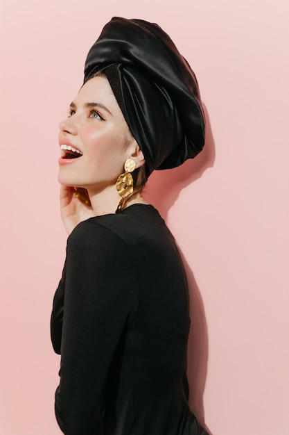 Mulher bonita rindo posando de turbante e brincos de ouro Foto gratuita
