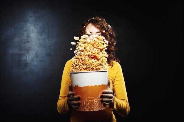 Mulher bonita se divertindo no cinema balançando balde de pipoca Foto gratuita