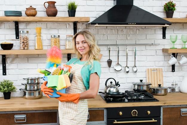 Mulher bonita, segurando, balde, de, limpeza, ferramentas, e, produtos, ficar, em, cozinha Foto gratuita