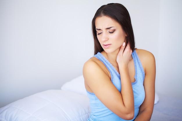 Mulher bonita, sentindo-se doente, tendo dor de cabeça, dor no corpo doloroso Foto Premium