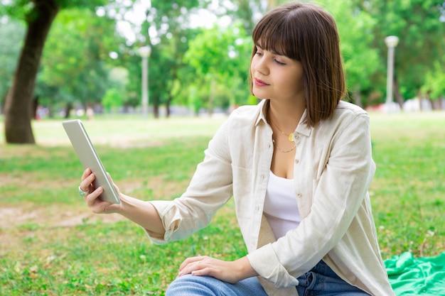 Mulher bonita séria que lê a notícia na tabuleta e que senta-se no gramado Foto gratuita