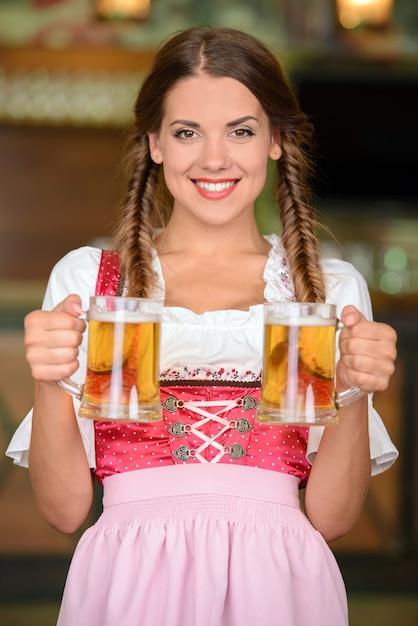 Mulher bonita, sexy garçom segurando copos de cerveja. Foto Premium