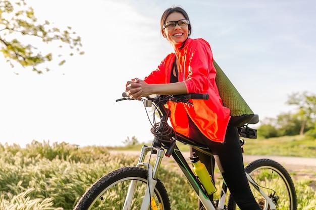 Mulher bonita slim fit praticando esportes de manhã no parque andando de bicicleta com tapete de ioga em roupa colorida de fitness, explorando a natureza, sorrindo, estilo de vida saudável e feliz Foto gratuita