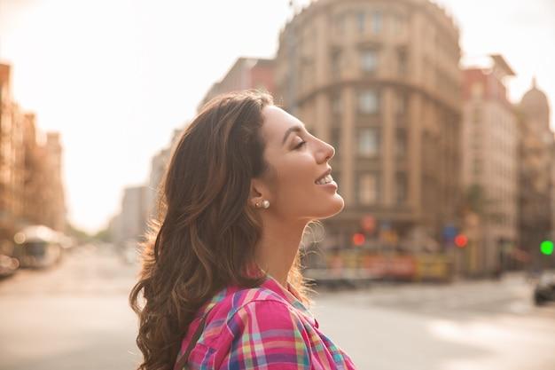 Mulher bonita sonhadora que aprecia a vida da cidade Foto gratuita