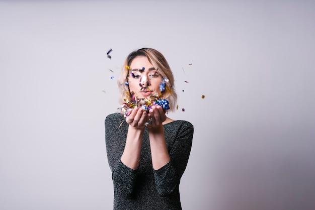 Mulher bonita, soprando, confetti Foto gratuita