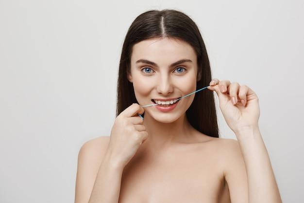 Mulher bonita sorridente passando fio dental dentes com fio dental Foto gratuita