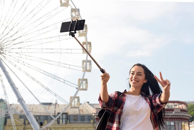 Mulher bonita sorridente tomando selfie com mostrando o gesto de vitória em pé perto da roda gigante Foto gratuita