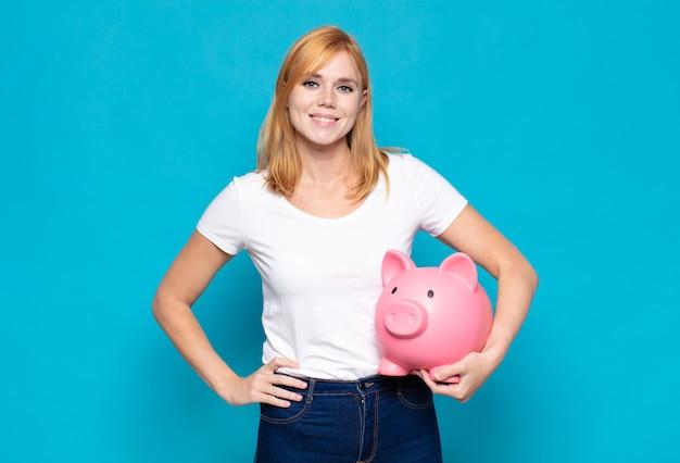 Mulher bonita sorrindo feliz com uma mão no quadril e atitude confiante, positiva, orgulhosa e amigável Foto Premium