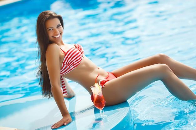 Mulher bonita, tendo um bronzeado natural perto da piscina. Foto Premium