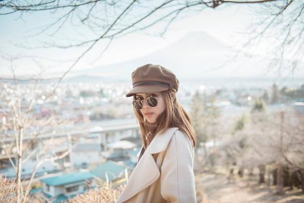 Mulher bonita turista sorrindo no pagode chureito e montanha fuji, japão Foto Premium