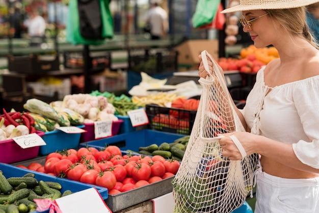 Mulher bonita usando sacola orgânica para vegetais Foto gratuita