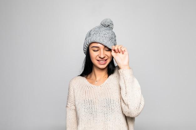 Mulher bonita, vestindo roupas quentes, retrato de inverno isolado na parede cinza. Foto gratuita