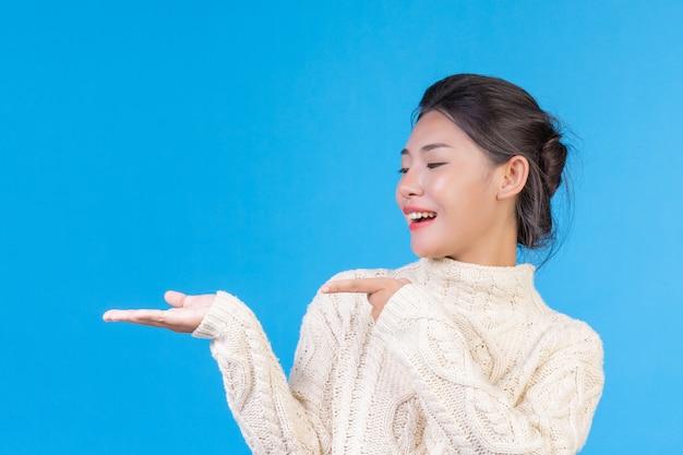Mulher bonita, vestindo um novo tapete branco de mangas compridas, mostrando um gesto em um azul. negociação. Foto gratuita