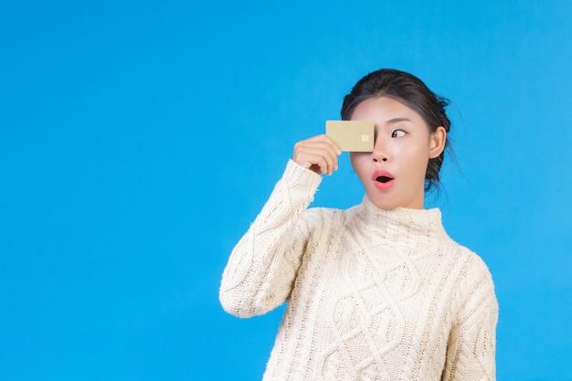 Mulher bonita, vestindo um novo tapete branco de mangas compridas, segurando um cartão de crédito dourado em um azul. negociação. Foto gratuita