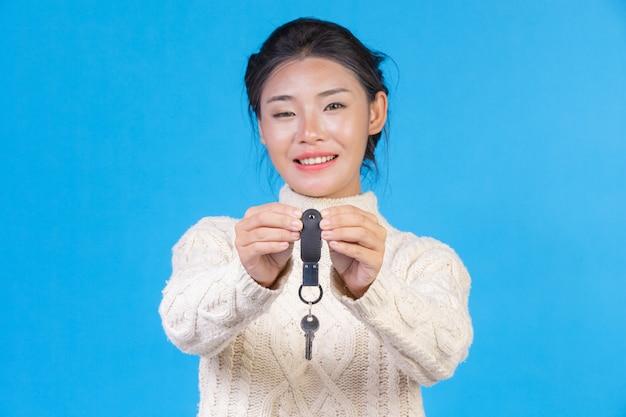 Mulher bonita, vestindo um novo tapete branco de mangas compridas, segurando um chaveiro na mão em um azul. negociação s. Foto gratuita