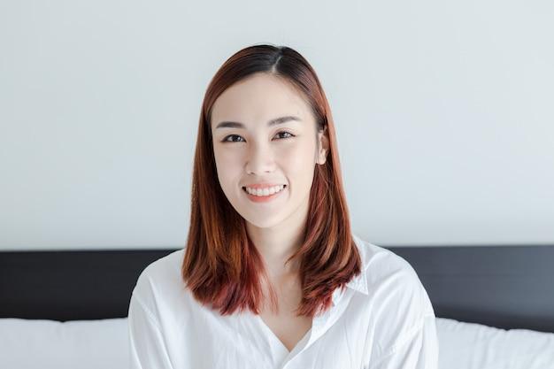 Mulher bonita vestir camisa branca sorrir no quarto de cama na manhã Foto Premium