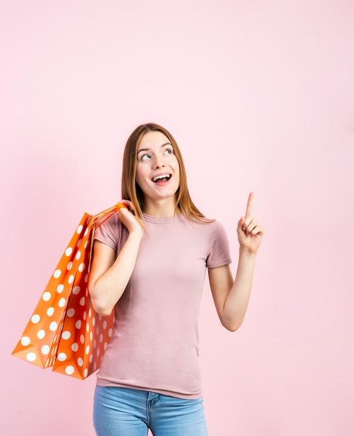 Mulher brincalhão em jeans com fundo rosa Foto gratuita