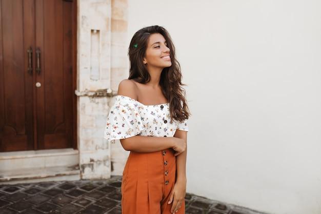 Mulher bronzeada em um elegante short laranja com cintura alta e blusa clara posando contra a parede da casa com portas de madeira antigas Foto gratuita