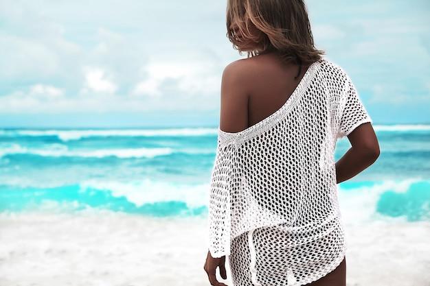Mulher bronzeada na blusa branca transparente andando na praia de verão Foto gratuita