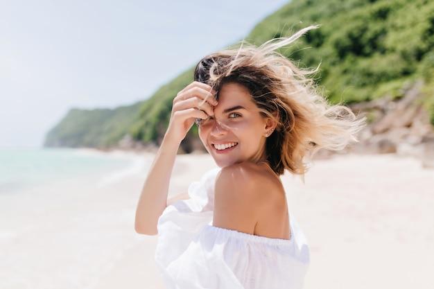 Mulher bronzeada sonhadora olhando por cima do ombro em pé na costa do mar. adorável mulher loira posando com prazer na ilha tropical em um dia quente. Foto gratuita