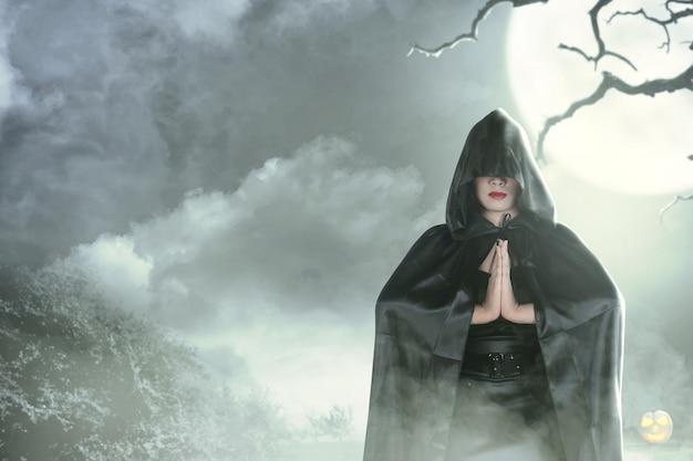 Mulher bruxa no encapuçado preto fazendo mágica ritual Foto Premium