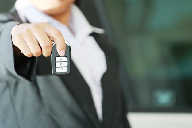 Mulher bussiness mostrar uma chave do carro remoto Foto Premium