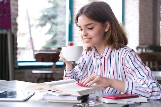 Mulher, café bebendo, e, leitura Foto gratuita