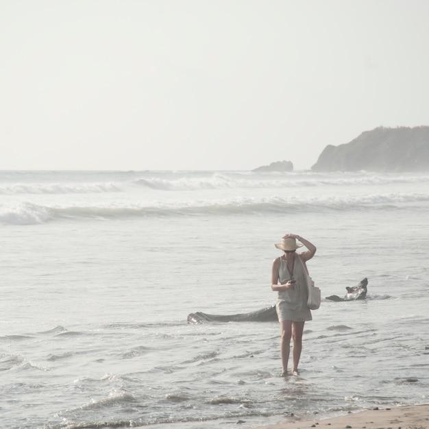 Mulher caminhando ao longo da beira-mar na costa rica Foto Premium