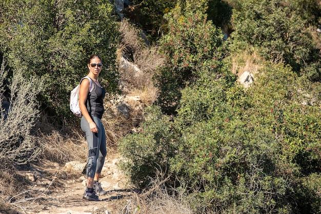 Mulher caminhando ao longo de um caminho no parque natural de peñon de ifach, em calpe, vestindo roupas esportivas Foto Premium