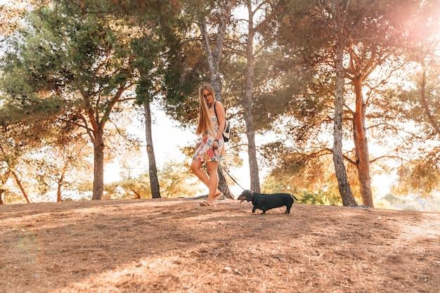 Mulher caminhando, com, dela, cão, em, jardim Foto gratuita