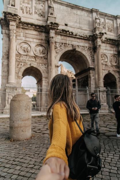 Mulher caminhando em direção ao arco de adriano com camisa amarela Foto Premium