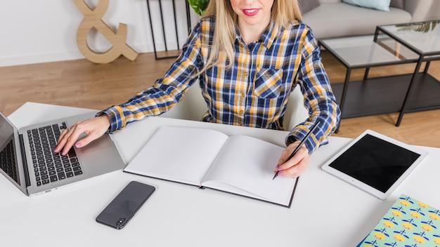 Mulher canhoto, escrevendo no caderno no local de trabalho com laptop Foto gratuita
