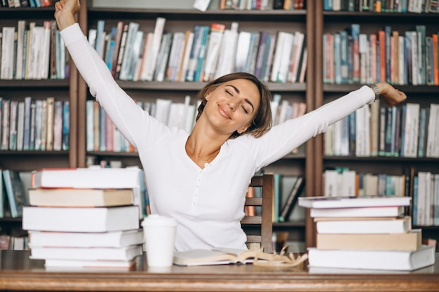 Mulher cansada alongamento na biblioteca Foto gratuita