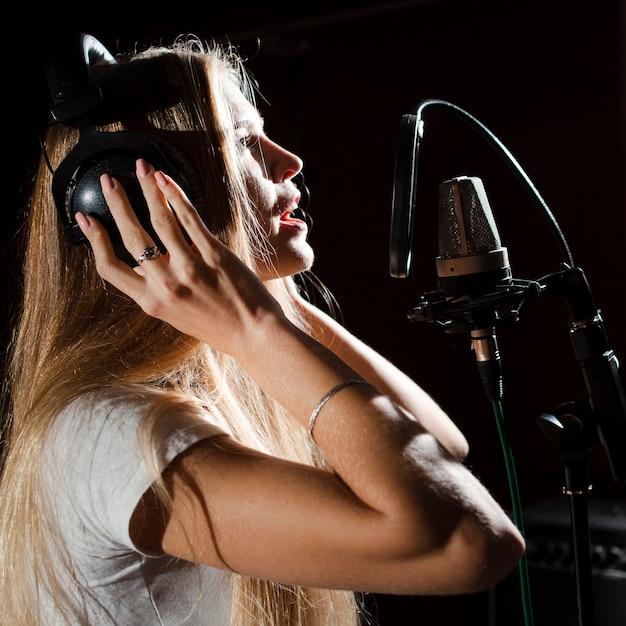 Mulher cantando no microfone e usando fones de ouvido Foto gratuita