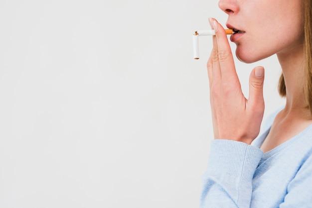 Mulher carregando cigarro quebrado sobre fundo branco Foto gratuita