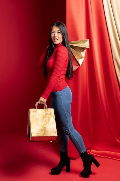 Mulher casual, posando com sacolas de papel para o ano novo chinês Foto gratuita