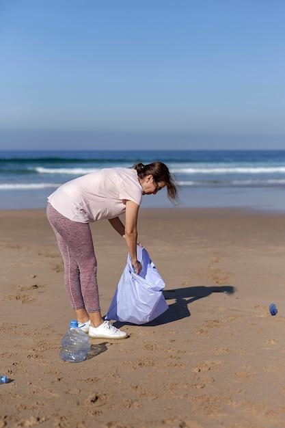Mulher catando lixo e plásticos, limpando a praia Foto Premium