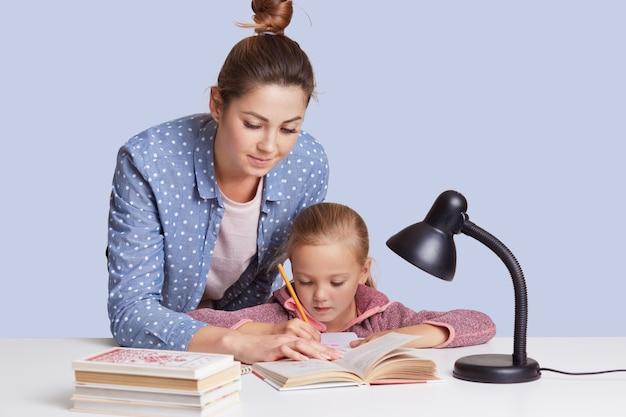 Mulher caucasiana, ajudando-a doughter a fazer lição de casa da escola, mãe e filho, rodeado por livros, uma menina sentada concentrada na mesa branca, tentando fazer somas. conceito de educação. Foto gratuita