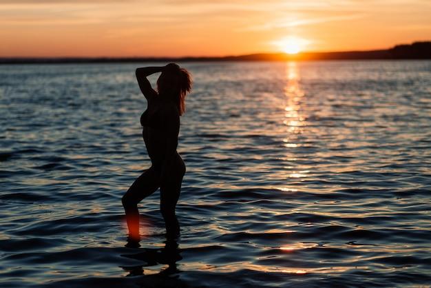Mulher caucasiana apta com esporte corpo está posando na praia ao pôr do sol. perda de peso no verão, motivação. Foto Premium