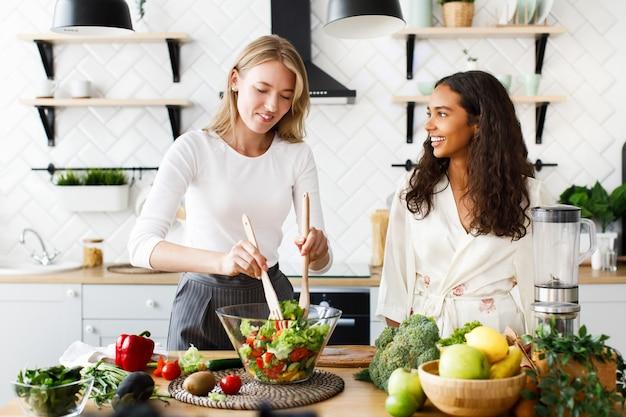 Mulher caucasiana atraente é cozinhar salada saudável e mulata bonita está olhando nela vestida de camisola de seda na cozinha projetada moderna Foto gratuita