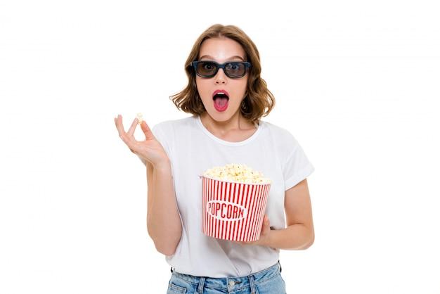 Mulher caucasiana chocada segurando pipocas usando óculos 3d Foto gratuita